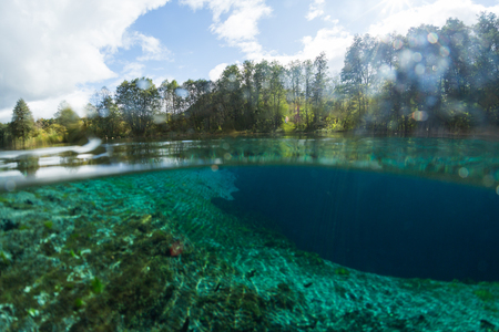 Split underwater view of the karst lake named Goluboye Ozero (Blue Lake) surrounded by forest. Maximum depth is 18m (60ft). Lake is situated near the city of Kazan, Russia