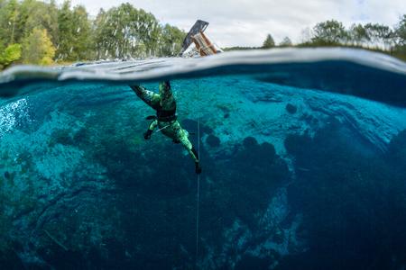 青い透き通った湖でのダイビングの男性のスプリット ショット