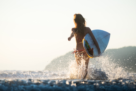 Woman with surfboard runs into the ocean with lots of splashes Zdjęcie Seryjne