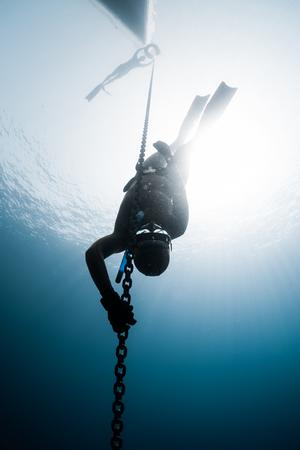 金属チェーンに沿って深さに降順フリーダイバー 写真素材