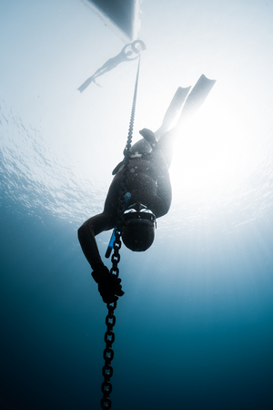 Freediver descending to the depth along the metal chain