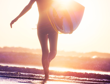 Woman with surfboard runs into the ocean during sunset