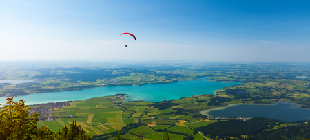 Paraglider flies over the green valley with lakes and towns. Area of the city of Fussen, Germany