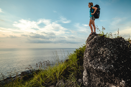 Lady hiker with backpack standing on the stone and enjoying sea view Stock Photo