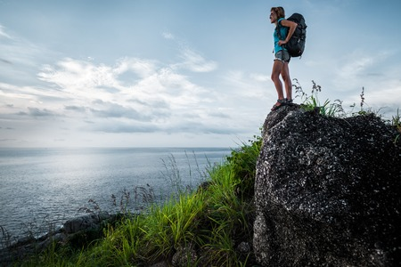 Lady hiker with backpack standing on the stone and enjoying sea view Stock fotó - 89524344