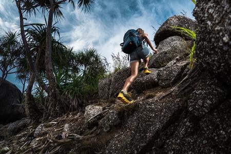 バックパックを持つ女性のハイカーは急な岩場を登る