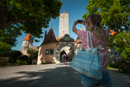 Young woman tourist walking in an old town of Rothenburg and taking a picture. Germany