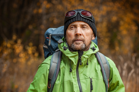 Mature backpacker in an autumn forest