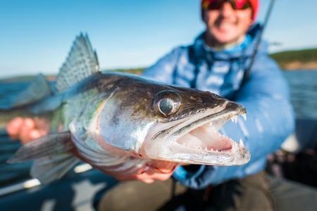 행복 한 낚시꾼 화가 보유 하 고 강물에 보트에 빠져들 물고기
