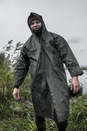 Man in a wetsuit and raincoat stands on the autumn meadow with grass