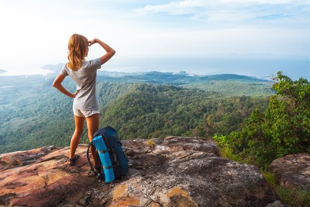 Young woman hiker stands on top of a mountain with raised hands and enjoys sunrise valley view