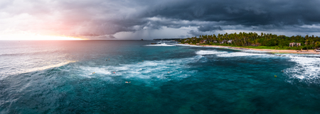 Panorama of the surf spot named Coconut with surfers on the line up. Stormy weather surfing conditions