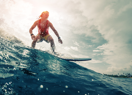 Young surfer rides the ocean wave Stock fotó