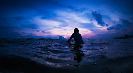Surfer waits the wave in an ocean during sunset