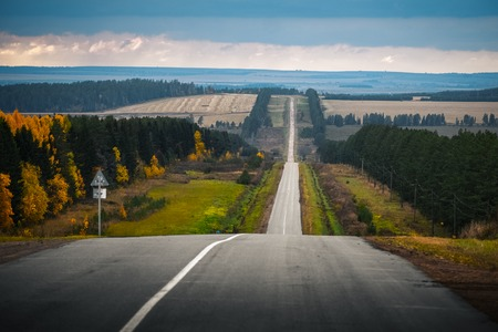Autumn uneven road through hilly terrain. Russia