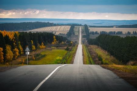Autumn uneven road through hilly terrain. Russia