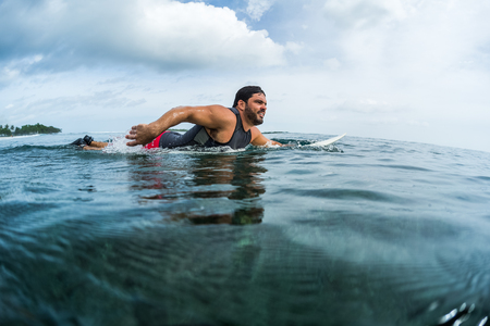 Muscular surfer with beard paddling in the ocean