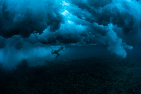 강력한 바다 물결 아래에서 다이빙하는 서퍼의 수중보기 스톡 콘텐츠