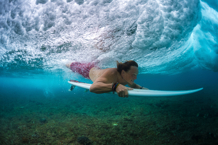 Young surfer make trick named Duck Dive to pass the ocean wave. Extreme sport and active lifestyle concept Imagens