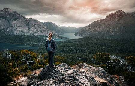 Woman hiker stands and enjoys valley view from viewpoint. Hiker reached top of the mountain and watching sunset. Patagonia, Argentina 免版税图像 - 93346933