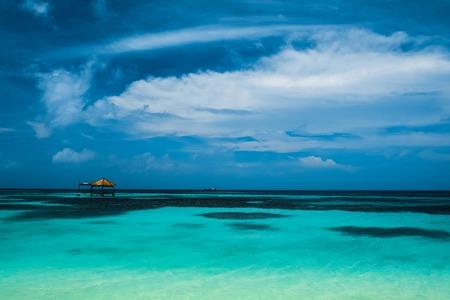 청록색 바다와 어두운 푸른 하늘 배경에 목조 건물. 몰디브 스톡 콘텐츠