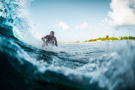 Young man rides the ocean wave. Extreme sport and active lifestyle concept