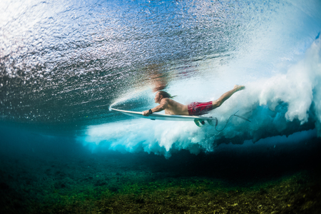 Young surfer dives under the ocean wave with surf board and performs trick named in surfing as a Duck Dive