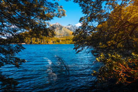Blue lake surrounded by forest and mountaind on the horizon. Area near the city of Bariloche, Argentina