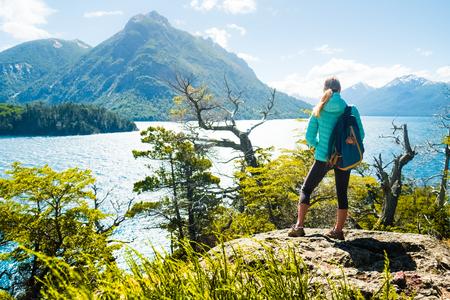 Vrouw wandelaar staat aan de kust van het meer en geniet van uitzicht op de bergen. Meerdistrict van Argentinië Stockfoto