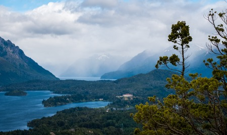 Lakes and mountains in the Lake district near the town of Bariloche, Argentina. Focus on the tree on foreground 写真素材