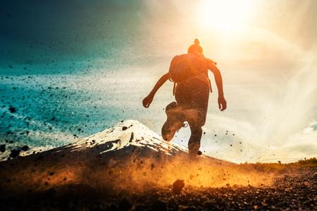 女性アスリートは、背景に火山と汚れたほこりっぽい地面に実行されます。山の中で運動するトレイルランニングアスリート