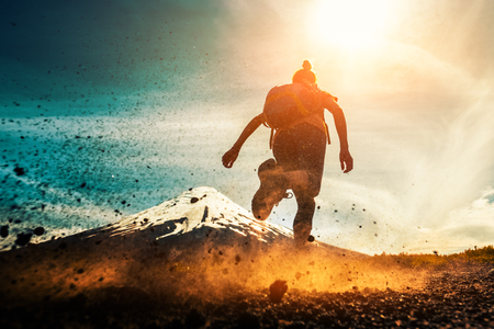 Woman athlete runs on a dirty and dusty ground with volcano on the background. Trail running athlete working out in the mountains Imagens