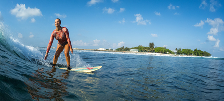 Happy surfer rides the ocean wave and smiles. Perfect sunny day, crystal clear water and tropical island on the background