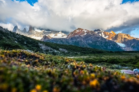 Mountains hidden in clouds and meadow with herbs on the foreground. Argentina