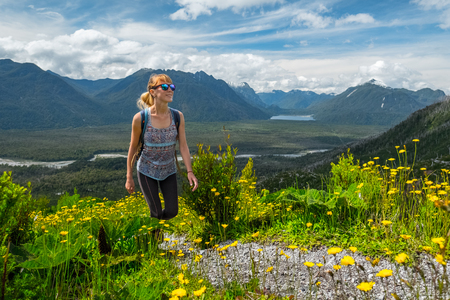 Woman hiker walks in the mountains during the sunny summer day Фото со стока - 97114312