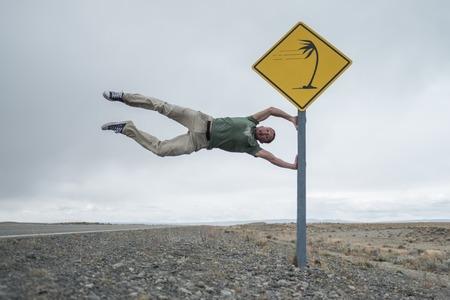 Hombre que se divierte con la señal de tráfico en la carretera patagónica en las latitudes de los cuarenta rugientes famosos por sus fuertes vientos. Argentina Foto de archivo