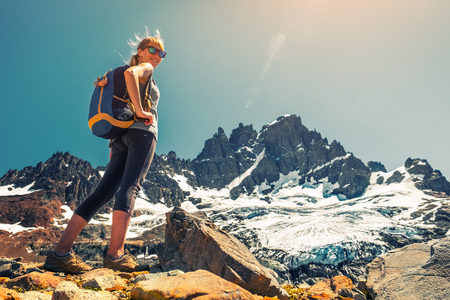 Woman hiker stands on the rocky ground with mountain and glacier on the background. Cerro Castillo mountain, Chile Stock Photo - 97067576
