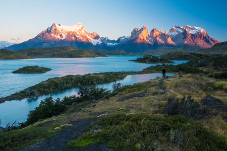 Torres del Paine National Park, lake of Pehoe with islets during sunrise. Two photographers are visible on top of the hill at right part of the frame