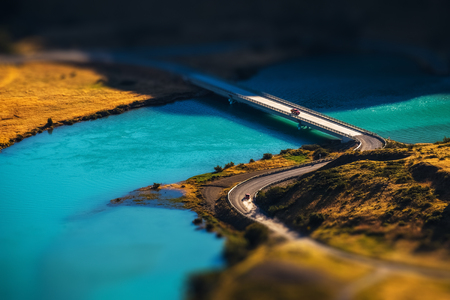 Two cars crossing blue river on the bridge. Chile. Tilt shift effect applied Stock fotó