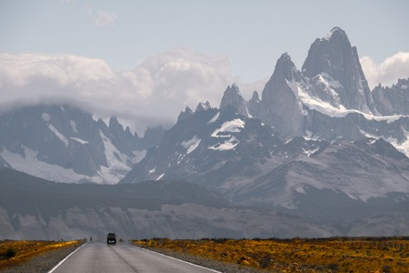 Car moves on an asphalt road with mountains on the background. Fitz Roy peak. Argentina