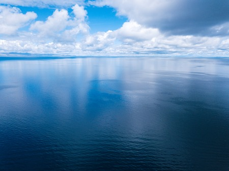 Aerial shot of the lake of Titicaca during sunny day with clouds in the sky. Bolivia