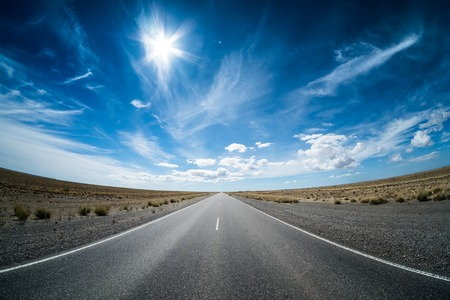 Asphalt road in the desert and sky with clouds. Road 3 (Ruta 3) through the Argentinean pampa. Imagens