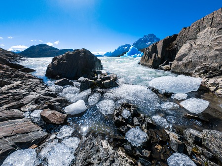 Ice pieces floating near the rocky coast. Glacier of Grey in Torres del Paine National Park, Chile 스톡 콘텐츠