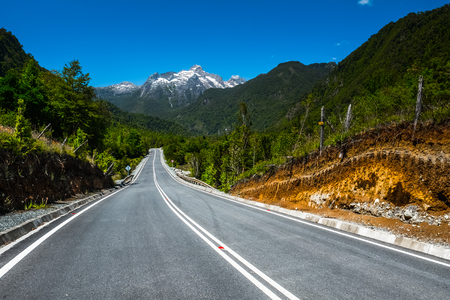Asphalt road with mountains on the background. Adventure road Carretera Austral (Ruta N7) near the town of Hornopiren, Chile Stock Photo