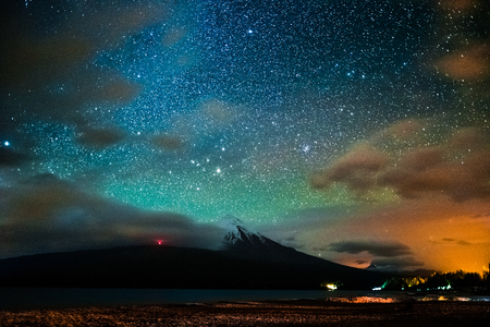 Starry sky and the volcano of Osorno with clouds highlighted by town, Chile. High level of noise Stok Fotoğraf