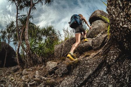 Woman hiker with backpack climbs steep rocky terrain