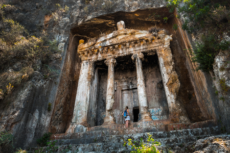 Amyntas rock tombs - 4th BC tombs carved in steep cliff. Tourist stands in front of the door. City of Fethiye, Turkey.