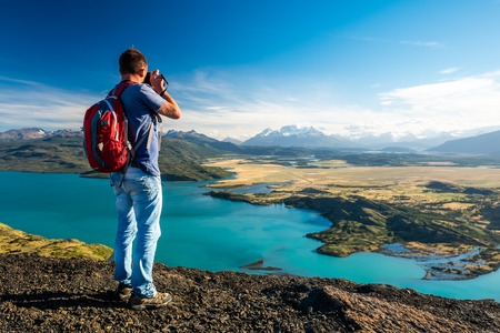 Photographer stands on top of a hill and takes photo of the valley with blue lake. Torres del Paine National Park, Chile. Imagens