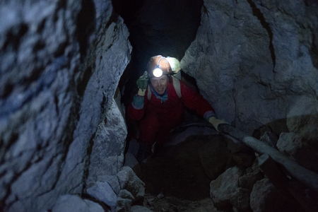 Lady tourist climbs rocks inside the cooperative mine located in the mountain of Cerro Rico near the city of Potosi, Bolivia. Image has high level of noise Stock fotó