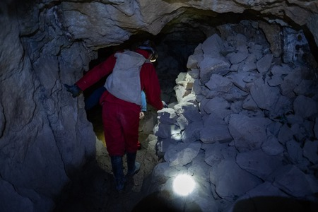 Tourist walks inside the cooperative mine in the city of Potosi, Bolivia. Image has high level of noise Stock Photo